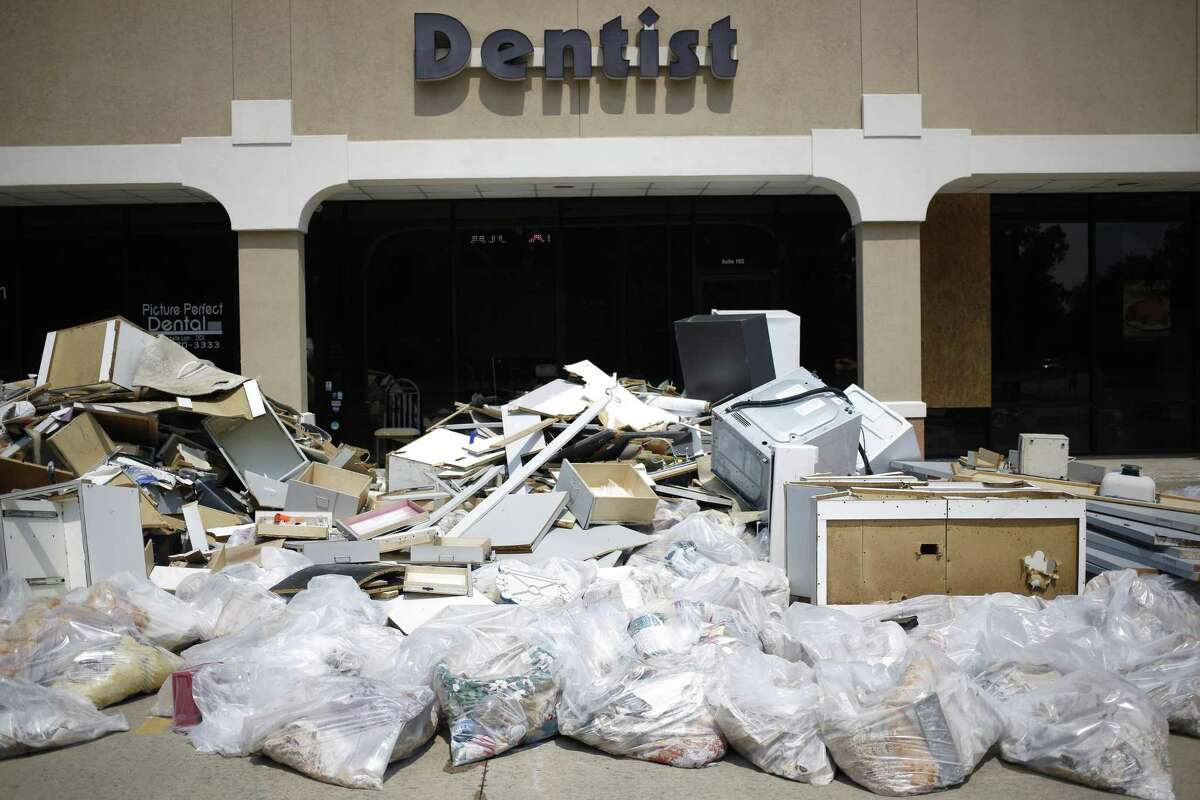 Debris sits piled up outside a dentist office that was damaged after flooding from Hurricane Harvey in Spring on Sept. 6. The Federal Reserve Bank of Dallas said a new survey indicated more than 40 percent of Texas companies were negatively affected by the hurricane.