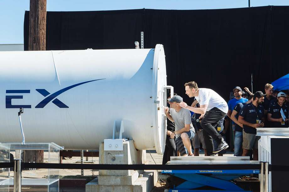 Elon Musk runs over to a small window on the SpaceX Tunnel to see the Munich team's WARR Hyperloop pod. Photo: JESSICA PONS, Special To The Chronicle