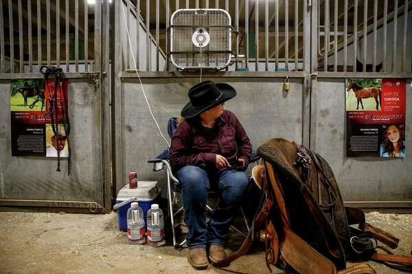 Deanna glances at Dakoda as he makes sounds in his stall while they rest between events;