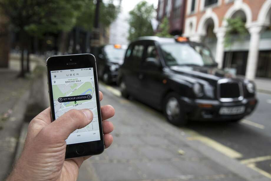 A rider uses the Uber app in London in 2014. London authori ties have decided not to renew Uber's license to operate. Photo: Oli Scarff