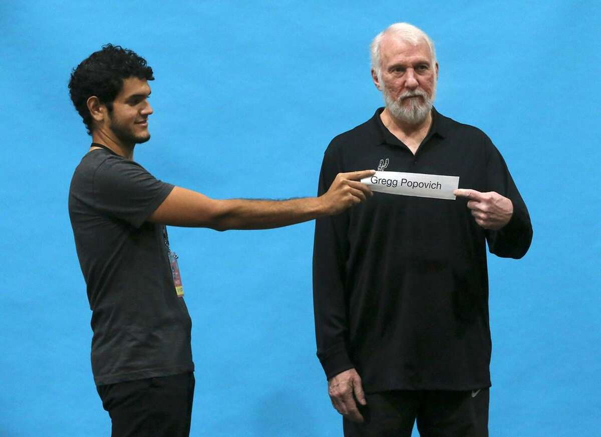 San Antonio Spurs coach Gregg Popovich gets ready for his portrait after a press conference during Spurs media day Monday September 25, 2017. Holding the name plate (left) is David Guel.