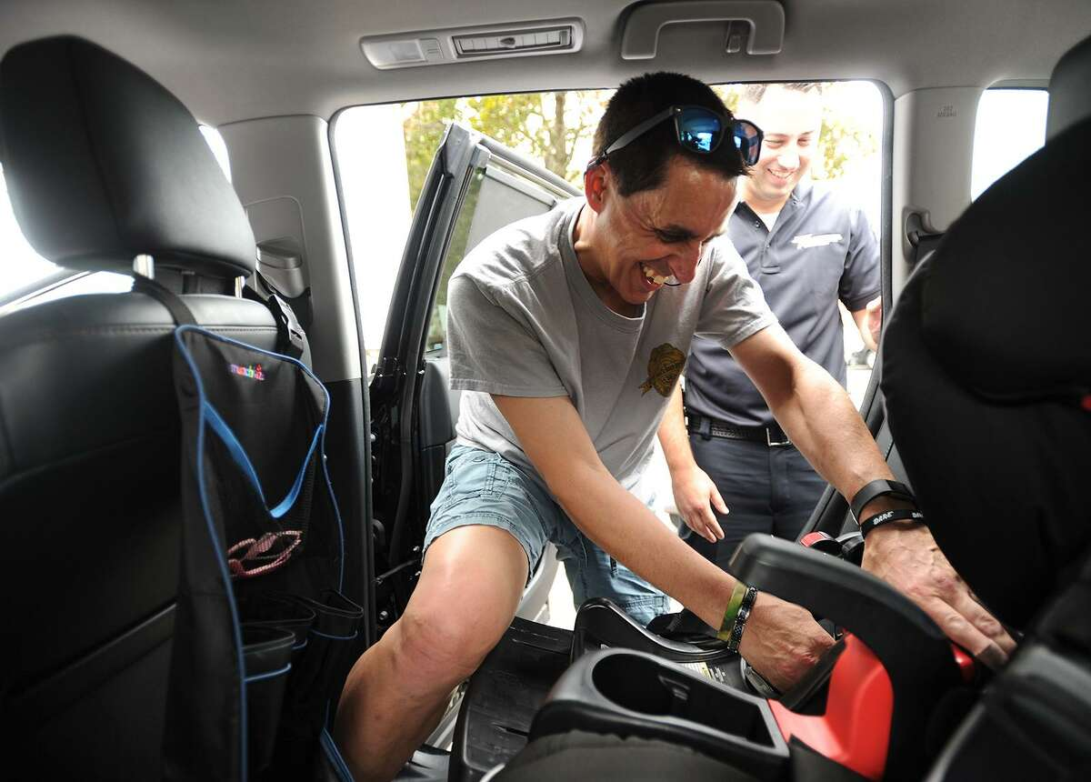 Easton Police Officer Mark Pastor installs a car seat during Griffin Hospital's Safe Kids Greater Naugatuck Valley Coalition's free Child Passenger Seat Check Clinic in Derby on Wednesday.