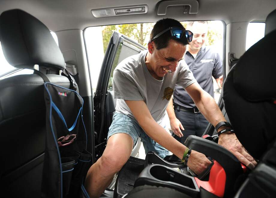 Easton Police Officer Mark Pastor installs a car seat during Griffin Hospital's Safe Kids Greater Naugatuck Valley Coalition's free Child Passenger Seat Check Clinic in Derby on Wednesday. Photo: Brian A. Pounds / Hearst Connecticut Media / Connecticut Post