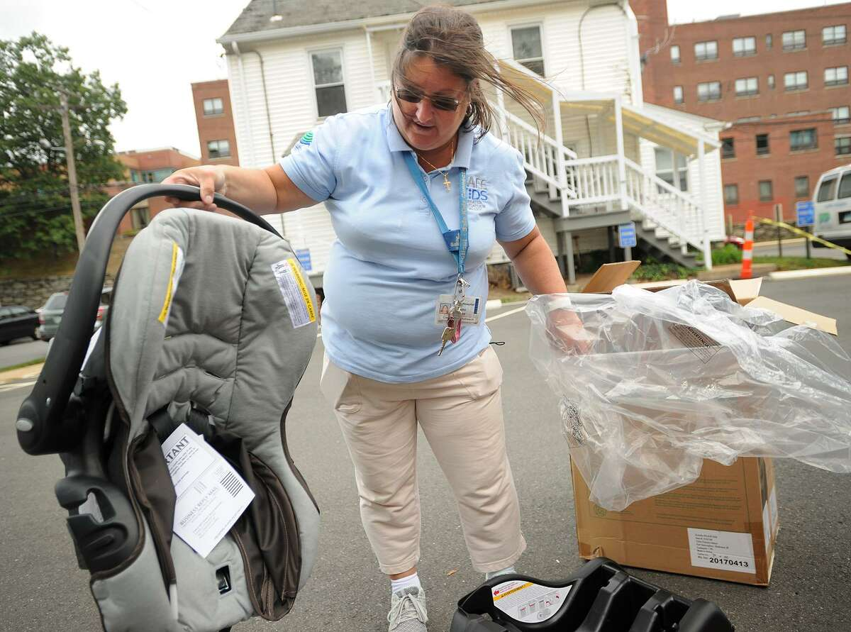Below, Safe Kids Greater Naugatuck Valley Coalition Coordinator Cathi Kellett donates a new car seat to a participant in the organization's free Child Passenger Seat Check Clinic outside Griffin Hospital in Derby, Conn. on Wednesday, September 20, 2017.