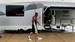 San Antonio Spurs guard Tony Parker walks through the rain outside of the team's practice facility during media day, Monday, Sept. 25, 2017, in San Antonio.