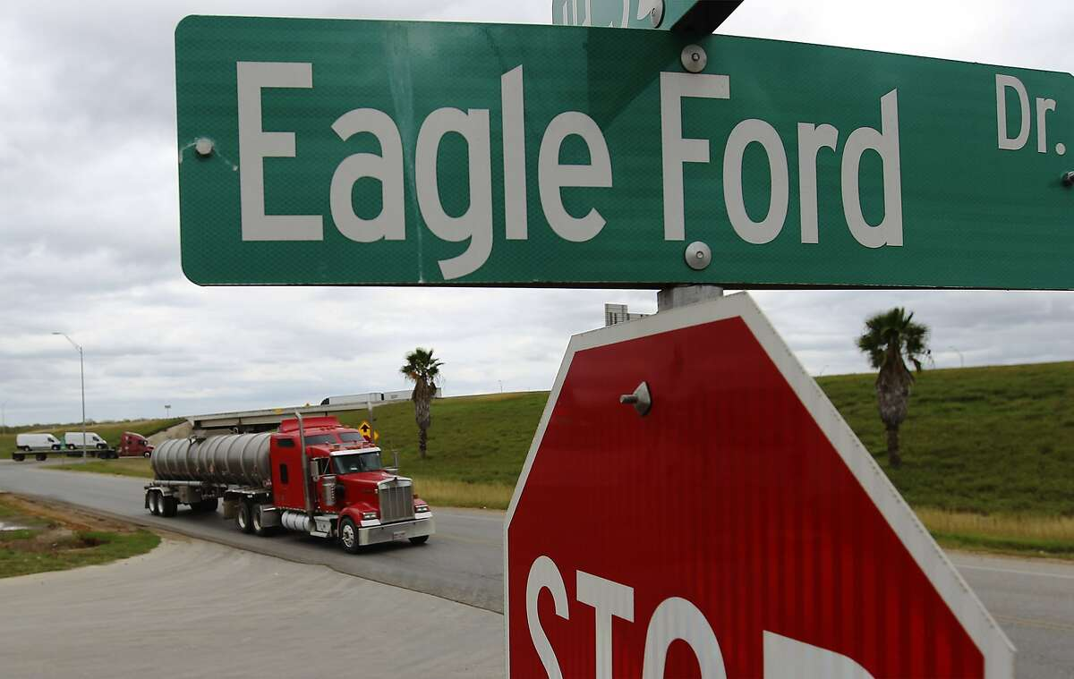 A tanker truck drives along the access road of Interstate 35 near Eagle Ford Drive in Cotulla, Texas on Thursday, Dec. 11, 2014. Commercial traffic has remained constant as oil production continues in the Eagle Ford region.