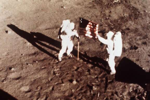 "Apollo 11 astronauts Neil Armstrong and Edwin E. ""Buzz"" Aldrin, the first men to land on the moon, plant the U.S. flag on the lunar surface, July 20, 1969. (AP Photo/NASA)"