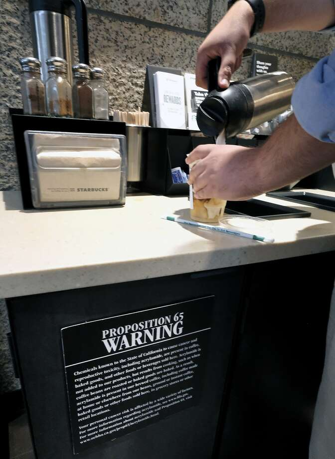 A customer pours milk into coffee near a posted Proposition 65 warning sign at a Starbucks coffee shop in Los Angeles. Photo: Richard Vogel, Associated Press