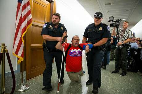 A protester who supports the Affordable Care Act is removed by U.S. Capitol Police during a Senate hearing on a 2017 proposal to repeal and replace the Affordable Care Act. The Department of Justice has just filed a brief in support of repealing the entirety of the Affordable Care Act in a case pending before the 5th Circuit Court in New Orleans.
