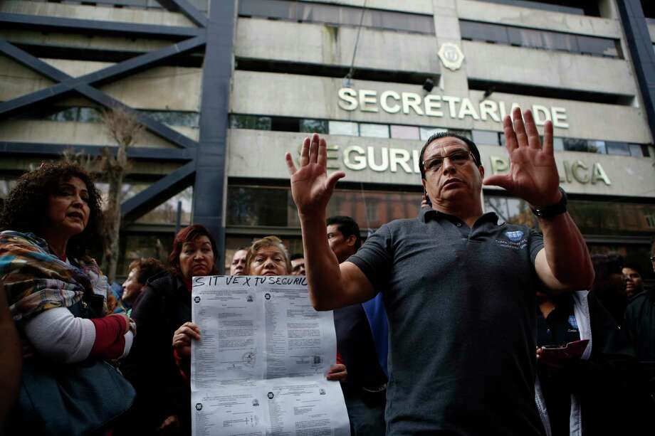People who work inside an office of the Secretary of Public Security organize in the street Monday as they collectively refuse to return to work inside the building they say suffered internal damage in last week's magnitude 7.1 earthquake. Photo: Rebecca Blackwell, STF / Copyright 2017 The Associated Press. All rights reserved.