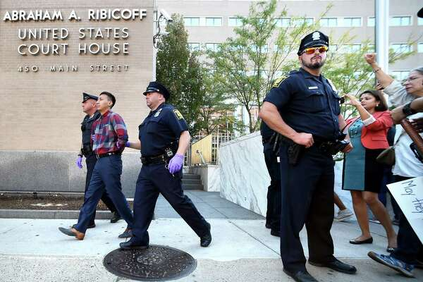 Jason Ramos of Meriden is arrested after blocking the entrance to the Abraham A. Ribicoff Federal Building and Courthouse in Hartford with other protesters on Monday to protest the imminent deportation of his parents.