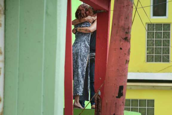 Residents in Old San Juan comfort one another as the community recovers from Hurricane Maria on Monday. The island of more than 3 million U.S. citizens is reeling in the devastating wake of Hurricane Maria.