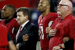 From left; Arizona Cardinals cornerback Patrick Peterson, president Michael Bidwill, wide receiver Larry Fitzgerald and head coach Bruce Arians stand during the national anthem prior to an NFL football game against the Dallas Cowboys, Monday, Sept. 25, 2017, in Glendale, Ariz. (AP Photo/Ross D. Franklin)