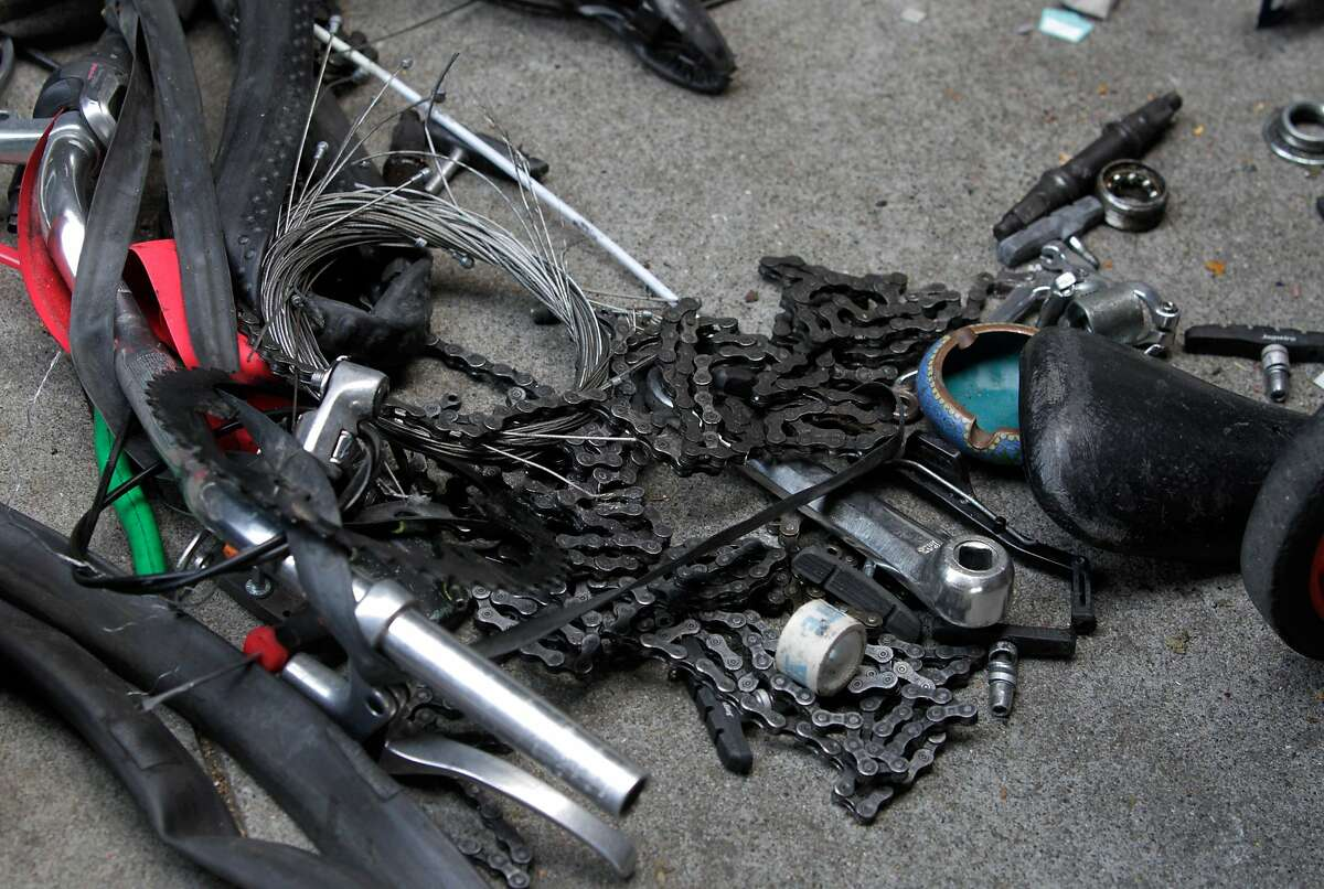 Bike parts are strewn out on the sidewalk while police officers question unidentified men about bicycles being dismantled below the Central Freeway on Duboce Avenue in San Francisco in 2014.