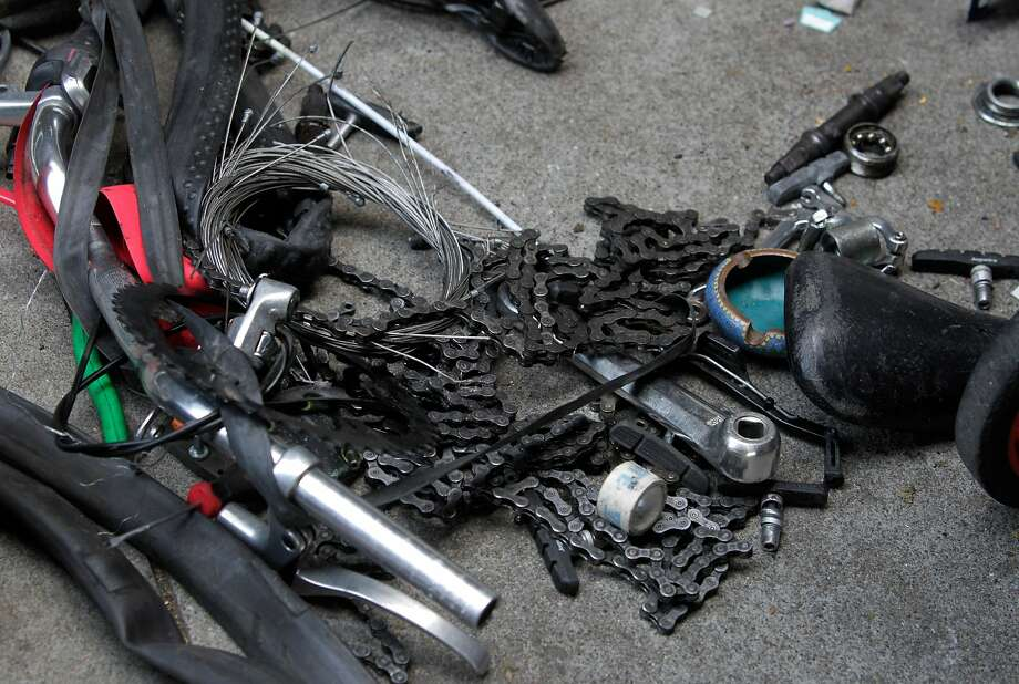 Bike parts are strewn out on the sidewalk while police officers question unidentified men about bicycles being dismantled below the Central Freeway on Duboce Avenue in San Francisco in 2014. Photo: Paul Chinn, The Chronicle