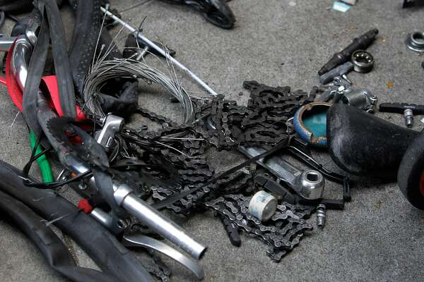 Bike parts are strewn out on the sidewalk while police officers question unidentified men about bicycles they were dismantling below the Central Freeway on Duboce Avenue in San Francisco, Calif. on Thursday, May 1, 2014. The bicycles were not reported stolen, so the men were released. While police suspect many of the bicycles may be stolen, few arrests are made since owners are reluctant to report them as stolen.