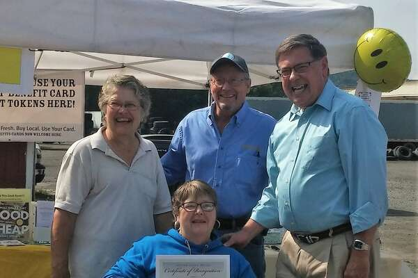 On Sept. 16 the Festival Farmers Market hosted an anniversary party in Cobleskill for all who visited  the market that day. Celebrating 21 years of service to the community, it is one of the longest running farmers markets in the state. In recognition, state Agriculture & Markets Commissioner Richard Ball attended as did Sen. James Seward who provided market owner and manager Donna Olsen with a certificate of appreciation for work in keeping the Festival Farmers Market a viable entity for easy access to local fresh farm products. Two agencies represented as they spread the message of good food equals good health: Bassett Health Care's  5.2.1.0  Every Day with Coordinator Chris Burrington and Schoharie Valley Farm to School Project/CCE with Project Director Regina Tillman. Free cake and ice cream was provided by The BlueShift PR & Promotions Group and Stewart's Shops. Shown are from right Seward, Ball, and Linda Cross, assistant and owner of Cripplebush Creek Farm. Seated is Olsen. (R/A Tillman-TBG)