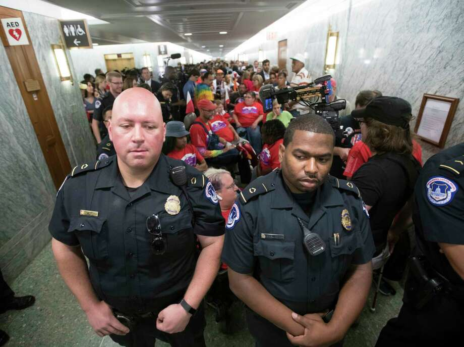U.S. Capitol Police maintain order as hundreds of people, many with disabilities, arrive for a Senate Finance Committee hearing on the last-ditch GOP push to overhaul the nation's health care system, on Capitol Hill in Washington, Monday, Sept. 25, 2017. (AP Photo/J. Scott Applewhite) Photo: J. Scott Applewhite, STF / Copyright 2017 The Associated Press. All rights reserved.