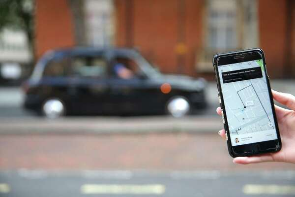 A smartphone shows the app for ride-sharing Uber in London. Greater London's transport authorities decided not to renew Uber's operating license last week.