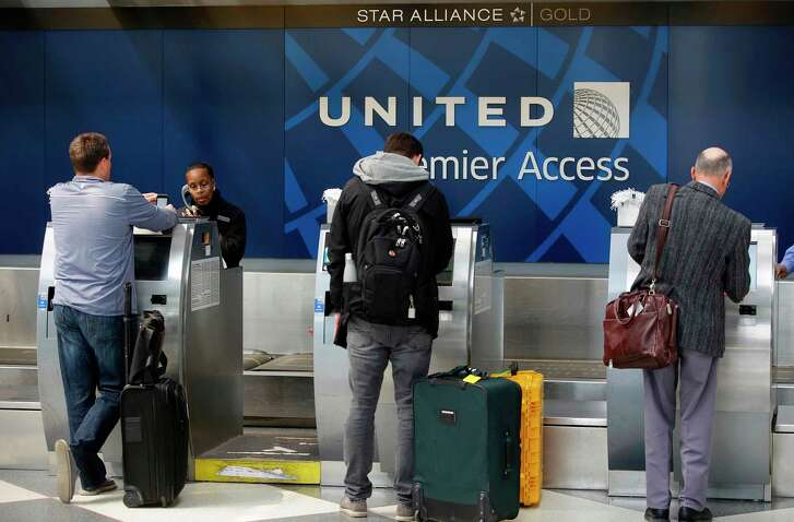 """(FILES) This file photo taken on April 12, 2017 shows  shows travelers as they check-in at the United Airlines Premier Access in Chicago, Illinois.  United Airlines on April 27, 2017 announced it will offer bumped passengers up to $10,000 in compensation and reduce overbooking following the dragging incident on board one of its flights that caused worldwide outrage. Those and other changes, which the airline called """"substantial,"""" are the result of a two-week internal probe of the April 9 incident, video of which went viral.   / AFP PHOTO / Joshua LOTTJOSHUA LOTT/AFP/Getty Images"""