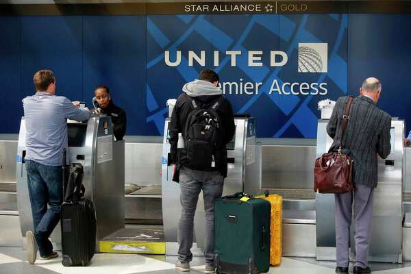 "(FILES) This file photo taken on April 12, 2017 shows  shows travelers as they check-in at the United Airlines Premier Access in Chicago, Illinois.  United Airlines on April 27, 2017 announced it will offer bumped passengers up to $10,000 in compensation and reduce overbooking following the dragging incident on board one of its flights that caused worldwide outrage. Those and other changes, which the airline called ""substantial,"" are the result of a two-week internal probe of the April 9 incident, video of which went viral.   / AFP PHOTO / Joshua LOTTJOSHUA LOTT/AFP/Getty Images"