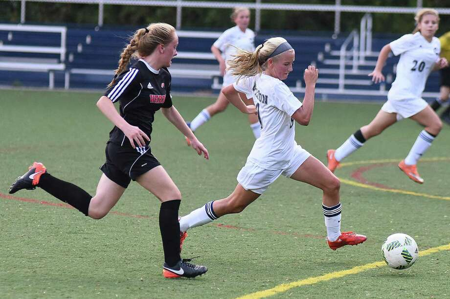 Wilton's Piper Chase, right, pushes the ball up field in front of Fairfield Warde's Lauren Tangney during the first half of Monday's FCIAC girls soccer game at Kristine Lilly Field in Wilton. Warde won 1-0 on Tangney's goal. Photo: John Nash / Hearst Connecticut Media / Norwalk Hour