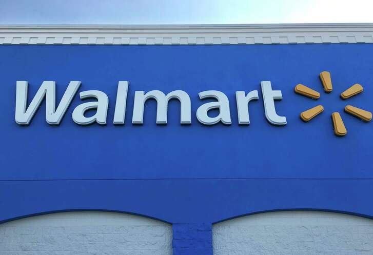 This Thursday, Jan. 5, 2017, photo shows corporate signage at a Walmart in Kissimmee, Fla. Walmart is testing a service that lets a delivery person walk into a customer's home when they're not there to drop off packages or put groceries in the fridge. The retailer says the service is for busy families who don't have time to stop at a store. (AP Photo/Swayne B. Hall)