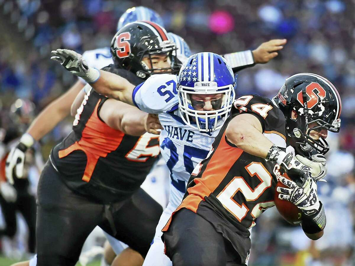 Darien's Mark Schmidt tackles Shelton's Keith Prior as the Wave defeat the Gaels, 39-7, to win the Class LL state football championship on Dec. 12, 2015, at New Britain Stadium atWillowbrook Park in New Britain.
