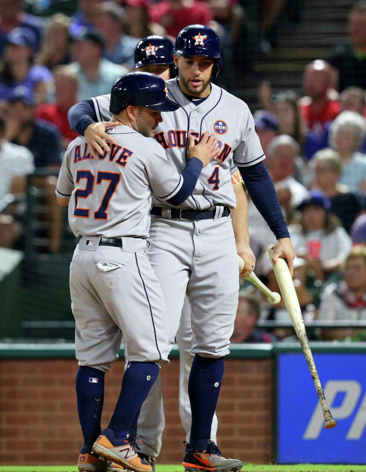 Houston Astros' Jose Altuve (27) and George Springer (4) celebrate after scoring a single by Marwin Gonzalez during the fourth inning against the Texas Rangers in a baseball game Monday, Sept. 25, 2017, in Arlington Texas. (AP Photo/Richard W. Rodriguez)