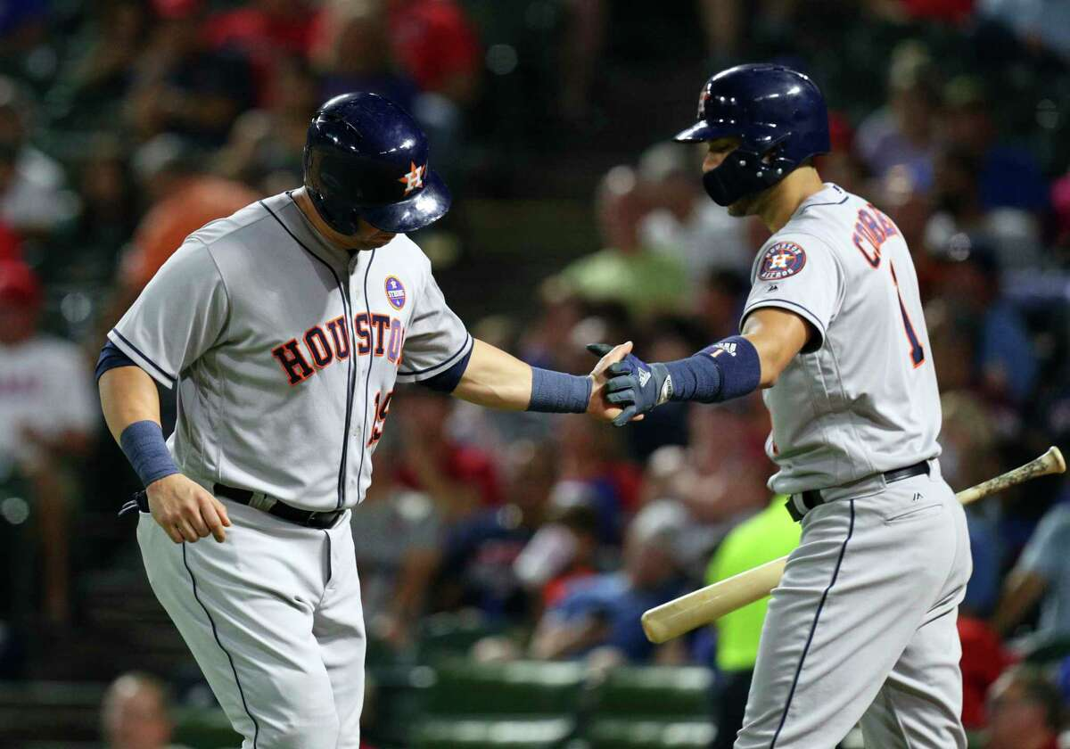 Houston Astros designated hitter Carlos Beltran (15) slaps hands with Carlos Correa (1) after scoring during the fourth inning against the Texas Rangers in a baseball game Monday, Sept. 25, 2017, in Arlington, Texas. (AP Photo/Richard W. Rodriguez)