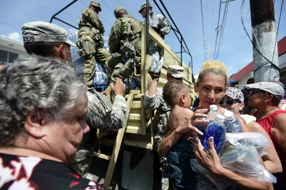 In this Sept. 24, 2017, photo, National Guard Soldiers arrive at Barrio Obrero in Santurce to distribute water and food among those affected by the passage of Hurricane Maria, in San Juan, Puerto Rico.  Federal aid is racing to stem a growing humanitarian crisis in towns left without fresh water, fuel, electricity or phone service by the hurricane. (AP Photo/Carlos Giusti) ORG XMIT: WX104 Photo: Carlos Giusti / Copyright 2017 The Associated Press. All rights reserved.