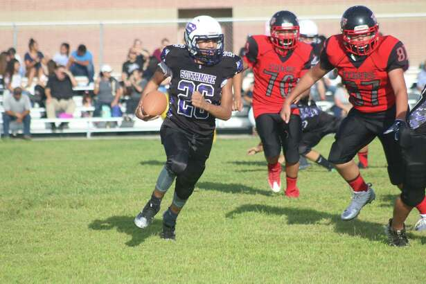 Southmore Intermediate's Ethan Torres looks for a running lane as a pair of Tigers give chase during first-half action Monday night. Torres finished with 80 yards rushing and 45 receiving in the 20-0 season-opening win.