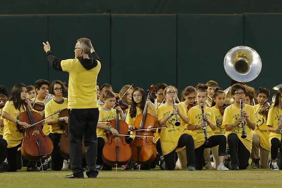 Members of the Oakland Unified School District Band kneel while performing the national anthem prior to a baseball game between the Seattle Mariners and the Oakland Athletics on Monday, Sept. 25, 2017, in Oakland, Calif. (AP Photo/Ben Margot)