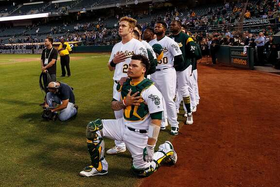 OAKLAND, CA - SEPTEMBER 25:  Bruce Maxwell #13 of the Oakland Athletics kneels during the national anthem in front of teammate Mark Canha #20 before the game against the Seattle Mariners at the Oakland Coliseum on September 25, 2017 in Oakland, California. (Photo by Jason O. Watson/Getty Images)