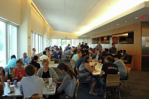 Workers throng the cafeteria in mid-September 2016 at 601 Merritt 7 in Norwalk, Conn., where FactSet Research has its headquarters offices. Over 12 months through August 2017, FactSet added about 700 employees to push its total workforce to 9,075 people in all.
