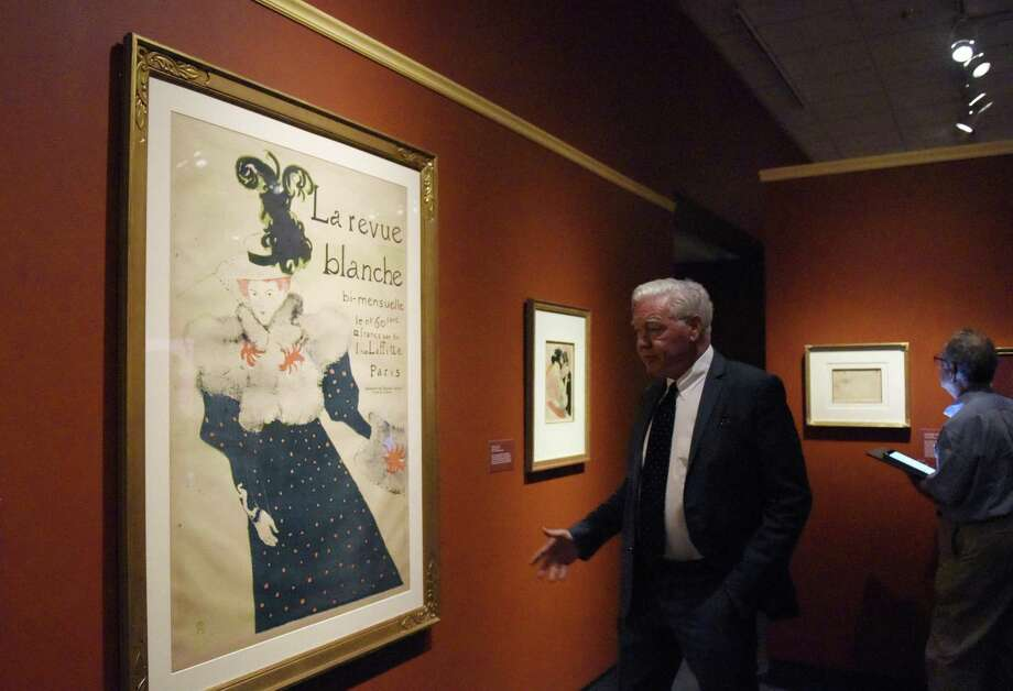 "Bruce Museum Executive Director Peter Sutton shows the lithograph ""La Revue Blanche"" at the new Henri de Toulouse-Lautrec exhibit at the Bruce Museum in Greenwich, Conn. Monday, Sept. 25, 2017. The show ""examines the relationship between portraiture, caricature, and rise of the cult of celebrity in the late 19th century, while focusing on the artist's portraits of entertainers who became icons of the Parisian nightlife."" The exhibit features 100 drawings, prints, and posters and will be up through Jan. 7, 2018. Photo: Tyler Sizemore / Hearst Connecticut Media / Greenwich Time"