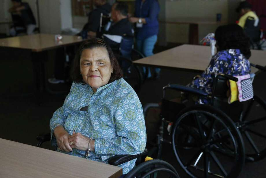 Catherine Araujo, 65, waits for live music in the community room at the Waters Edge skilled nursing facility July in Alameda, Calif. Long-term care costs can impose a crushing financial burden on individuals or families in part because private health insurance and Medicare offer only limited help. Photo: Leah Millis /San Francisco Chronicle / Leah Millis/ The Chronicle