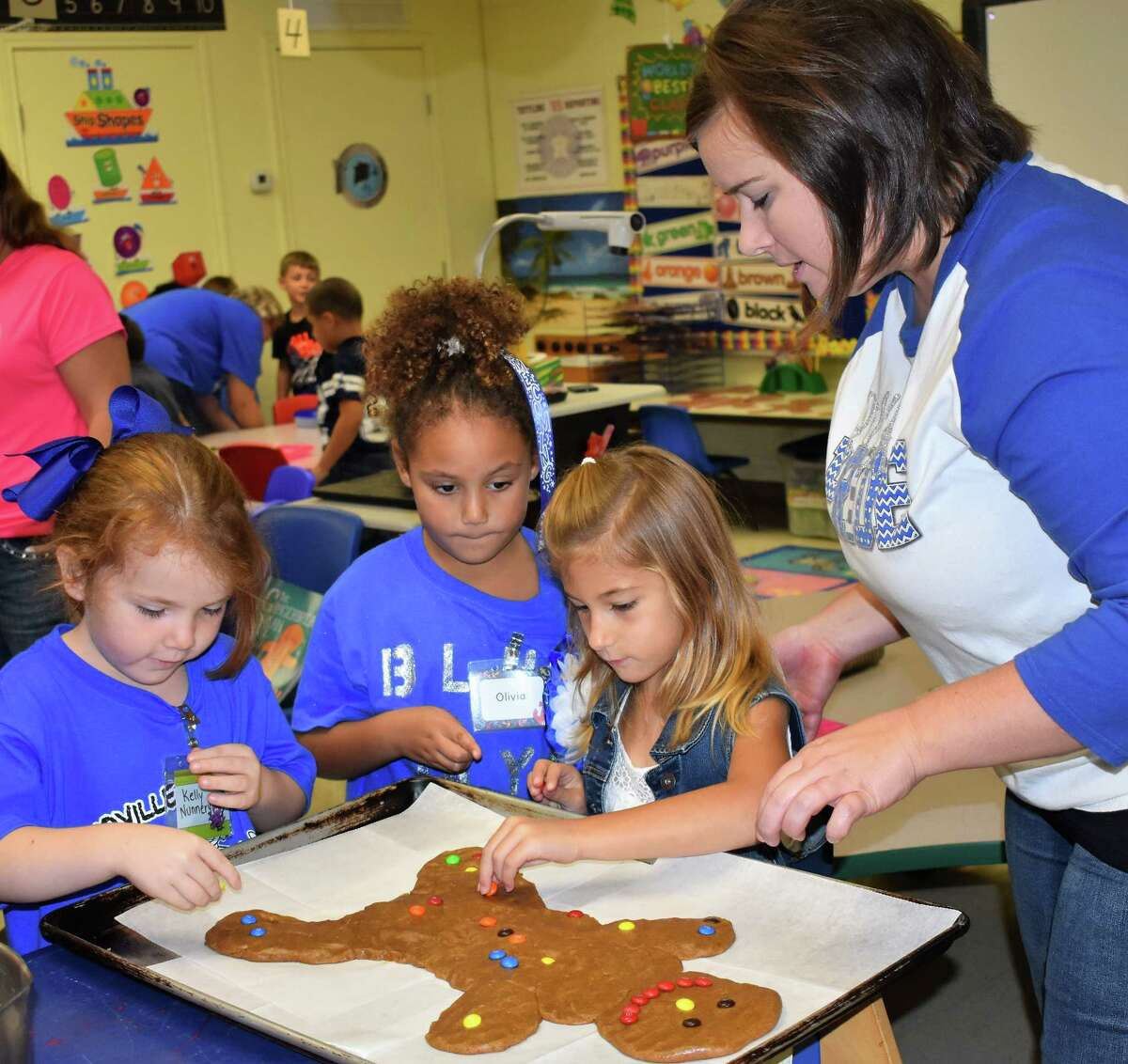 From left, Needville kindergartners Kelly Nunnery, Olivia Craddock and Tori Hundl carefully place M&s on a gingerbread man as teacher Whitney Anderson assists. At the beginning of each school year, kindergarten teachers at the campus use the book Â?