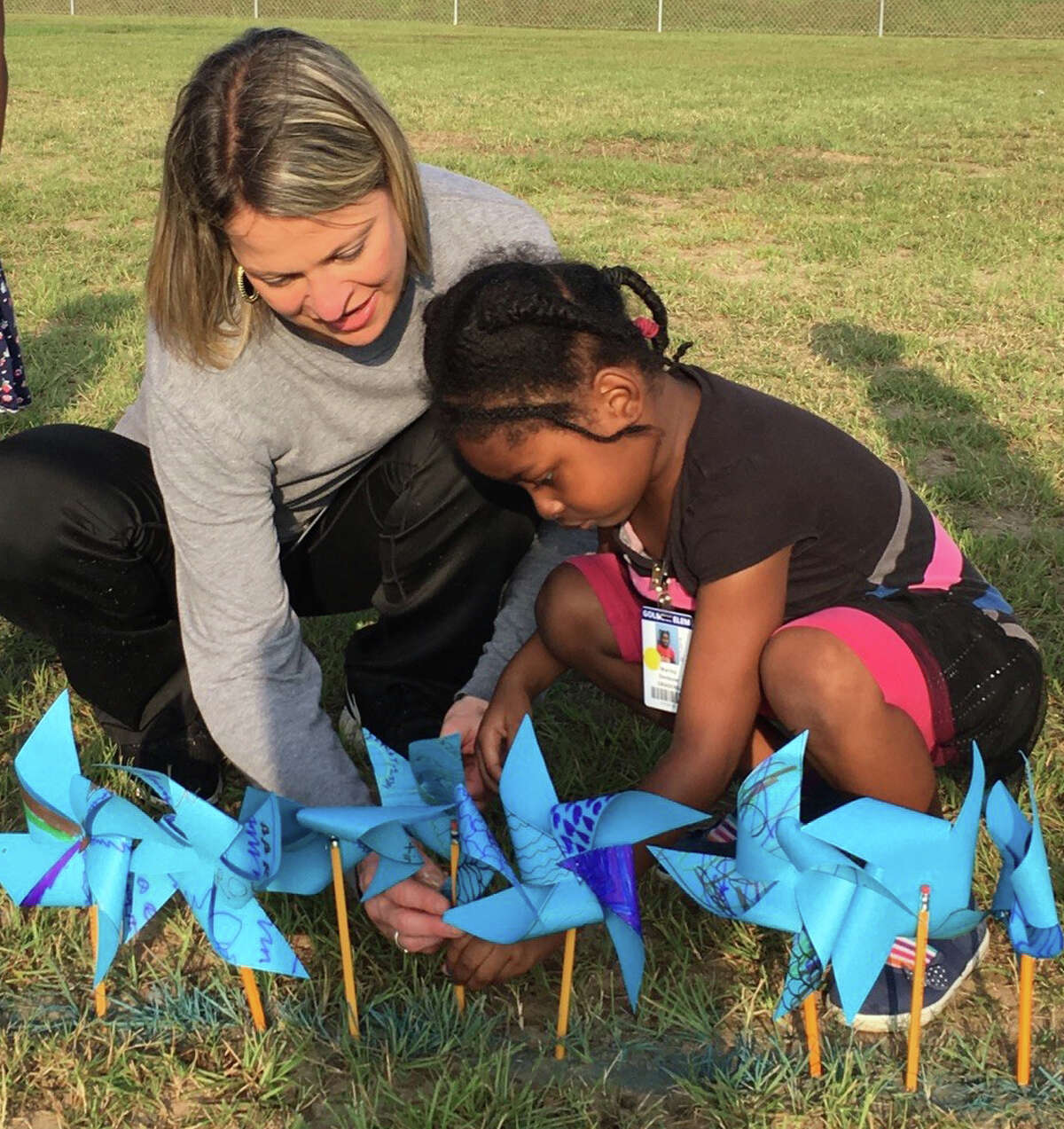 Golbow Elementary School physical education aideShana Robisch helps kindergartner Mercy Denbow place her pinwheel as part of the