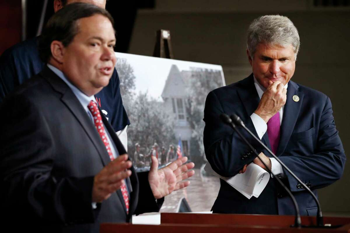 Rep. Blake Farenthold, R-Texas, left, speaks as Rep. Michael McCaul, R-Texas, listens during a news conference with members of the Texas delegation about the emergency funding bill for Harvey relief efforts, Wednesday, Sept. 6, 2017, on Capitol Hill in Washington. Behind them is a photograph of Harvey flooding in the Houston area. (AP Photo/Jacquelyn Martin)