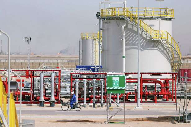An Iraqi labourer rides a bike in the newly opened section at the oil refinery of Zubair, southwest of Basra in southern Iraq, on March 3, 2016. Iraq's oil exports and revenue dipped in February compared with the previous month as low global crude prices offered Baghdad no financial respite, a statement said on March 1. Iraq's federal government exported a total of 93,536,000 barrels of crude last month, which amounts to a lower daily average than January, the oil ministry said. / AFP / HAIDAR MOHAMMED ALIHAIDAR MOHAMMED ALI/AFP/Getty Images