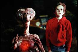 "Henry Thomas as Elliott, 10, stands alongside his co-star in the movie that changed his life, ""E.T. The Extra-Terrestrial."""