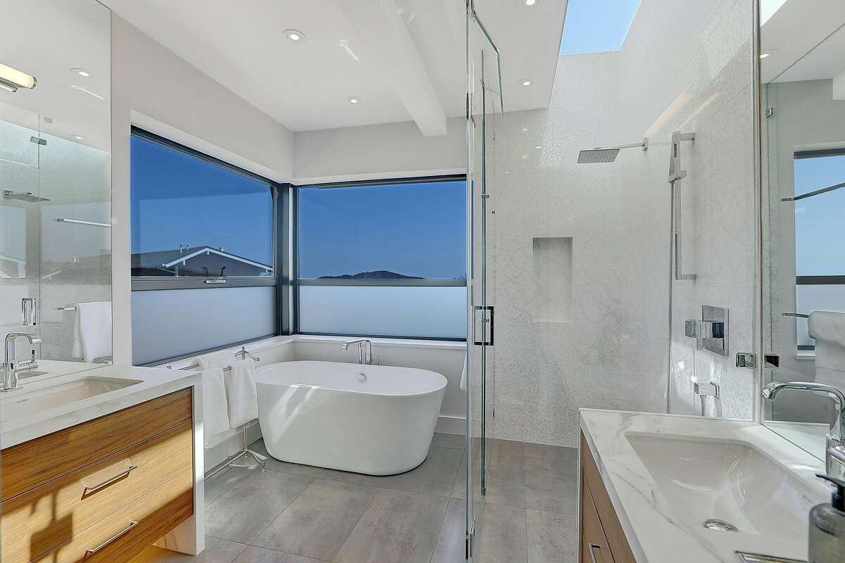 The master bathroom boats a soaking tub and vanities with waterfall edges.