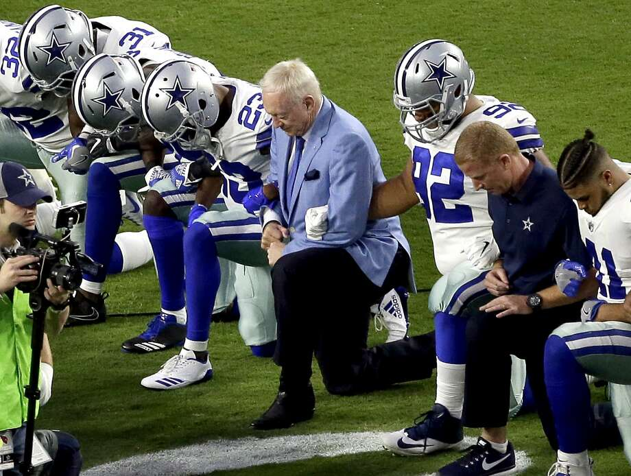 FILE - In this Monday, Sept. 25, 2017, file photo, the Dallas Cowboys, led by owner Jerry Jones, center, take a knee prior to the national anthem before an NFL football game against the Arizona Cardinals in Glendale, Ariz. What began more than a year ago with a lone NFL quarterback protesting police brutality against minorities by kneeling silently during the national anthem before games has grown into a roar with hundreds of players sitting, kneeling, locking arms or remaining in locker rooms, their reasons for demonstrating as varied as their methods. (AP Photo/Matt York, File) Photo: Matt York, Associated Press