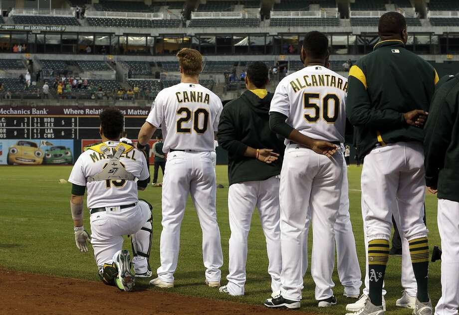 Oakland Athletics' Mark Canha (20) places his hand on the shoulder of Bruce Maxwell as Maxwell kneels during the national anthem for the third consecutive day, prior to the team's baseball game against the Seattle Mariners on Monday, Sept. 25, 2017, in Oakland, Calif. (AP Photo/Ben Margot) Photo: Ben Margot, Associated Press