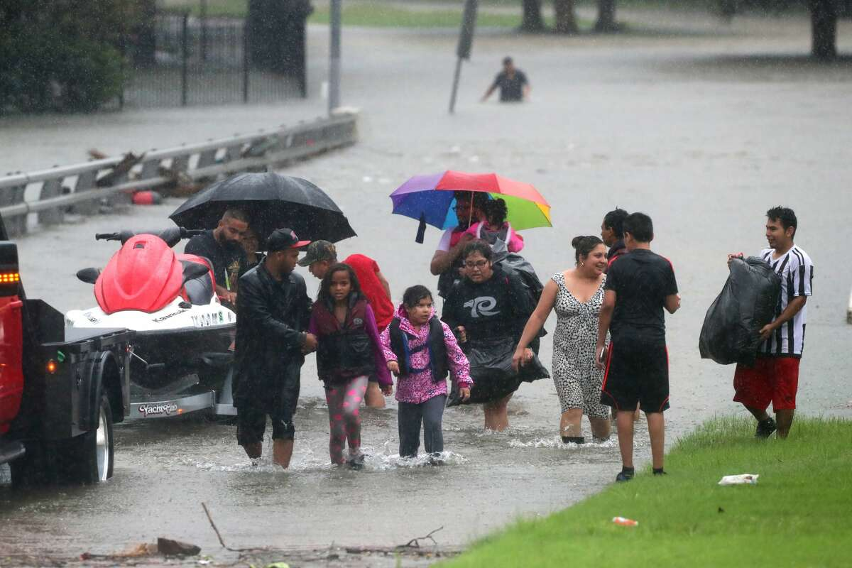Families walk away from the flooded apartment complex Bayou Parc at Oak Forest by the White Oak Bayou, Sunday, Aug. 27, 2017, in Houston. ( Marie D. De Jesus / Houston Chronicle )