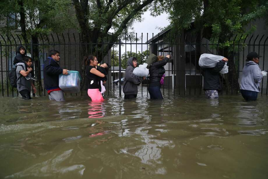 Flood survivors might find surprising strength in seeing themselves as one striving community. In this photo: Residents from Bayou Parc in Oak Forest evacuate the complex during Harvey. Photo: Marie D. De Jesus/Houston Chronicle