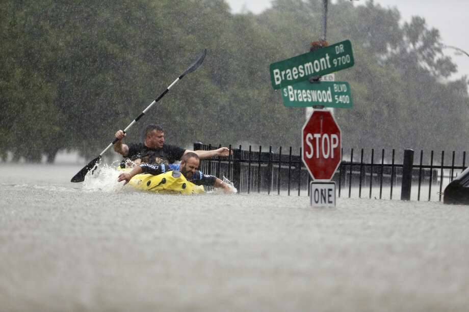 Hilell Tayer and Alex Gonik try to beat the current pushing them down an overflowing Brays Bayou along S. Braeswood in Houston, Texas, Sunday, Aug. 27, 2017. Rescuers answered hundreds of calls for help Sunday as floodwaters from the remnants of Hurricane Harvey climbed high enough to begin filling second-story homes, and authorities urged stranded families to seek refuge on their rooftops. (Mark Mulligan/Houston Chronicle) Photo: Mark Mulligan/Houston Chronicle
