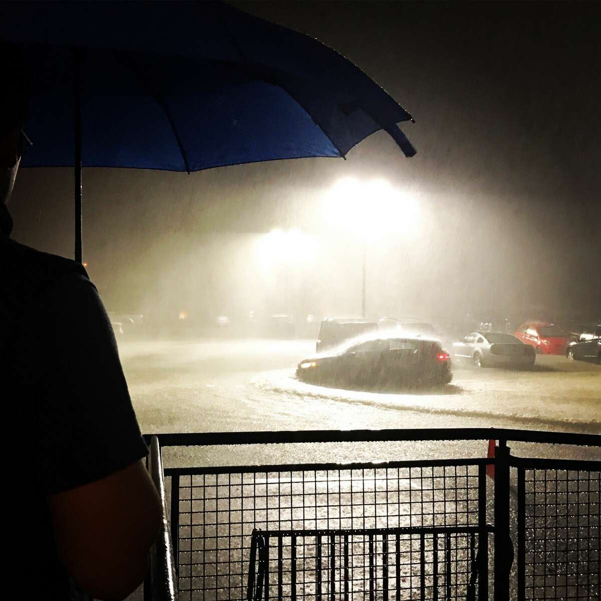 An apartment resident watches water accumulate in his parking lot as the rain continues to fall in Houston as a result of Hurricane Harvey on Saturday, August 26, 2017. (Elizabeth Conley/Houston Chronicle)