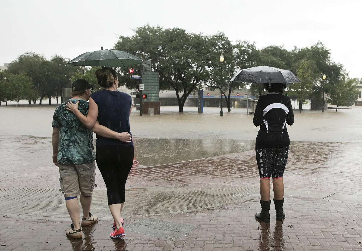 Onlookers check out the flooding on Fanin and Congress Streets in downtown Houston as Hurricane Harvey inches its way through the area on Sunday, Aug. 27, 2017. ( Elizabeth Conley / Houston Chronicle )